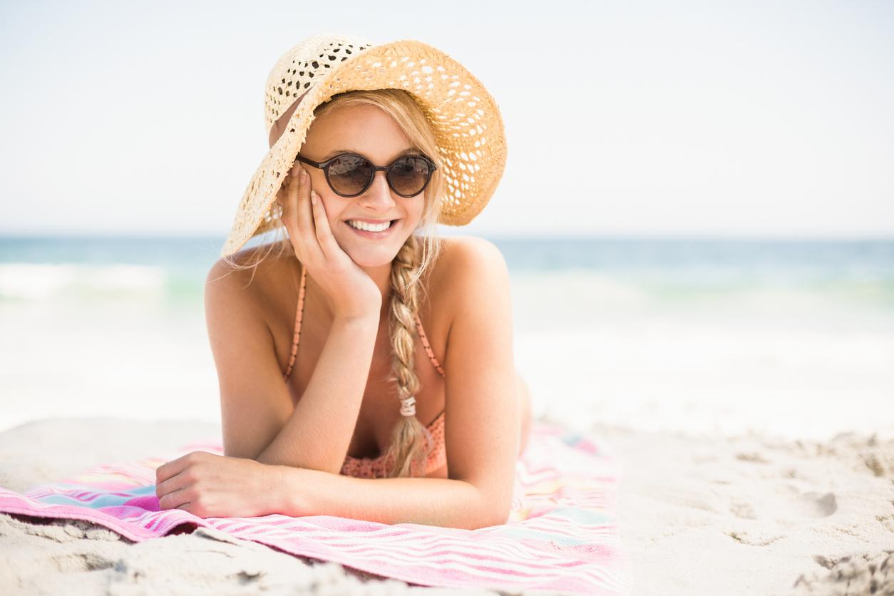 une femme allongé sur sa serviette de plage avec une tresse et un chapeau