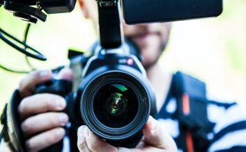 journaliste tient appareil photo réflex numérique en gros plan